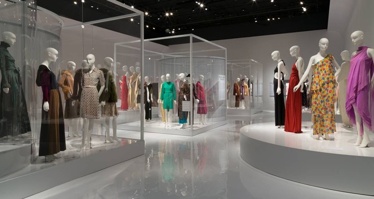 a room full of mannequins dressed in various colorful dresses at a museum