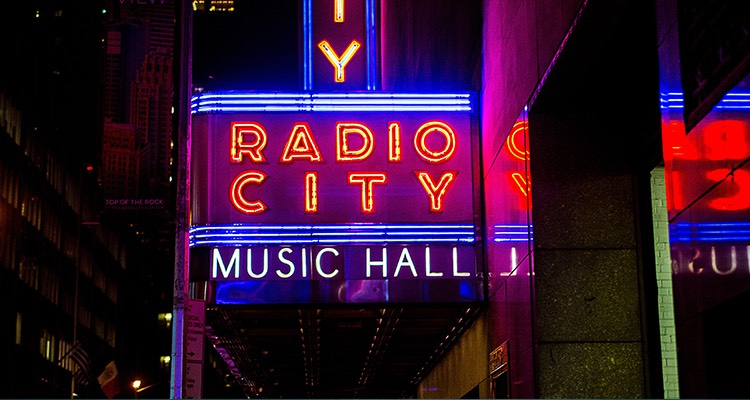 radio city music hall sign lit up in neon lights at night