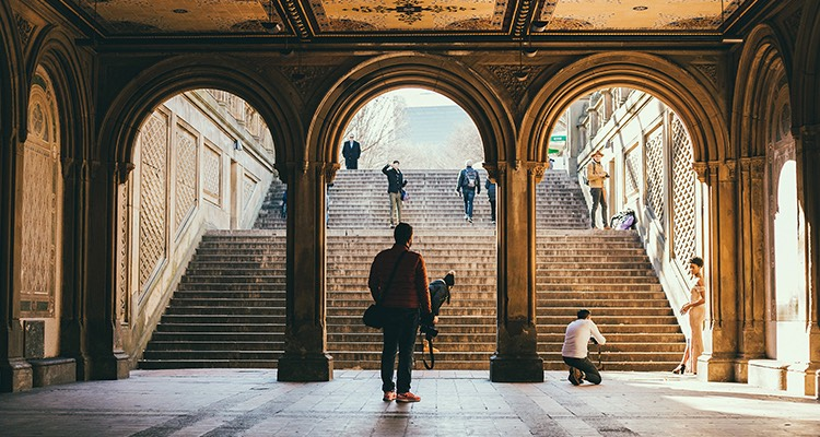 A man standing underneath an arched walkway in front of a row of wide steps in central park