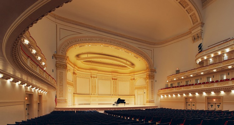 an black grand piano sits alone on stage at Carnegie hall with empty black theatre seats