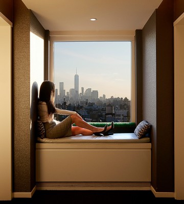 Woman sitting on seat next to window with skyline view