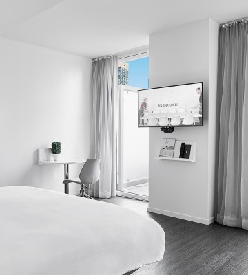 Room with king bed, white decor, tv and city view