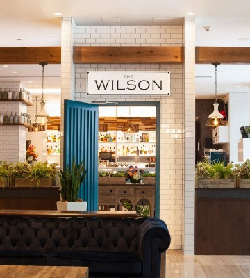 Entrance to Wilson restaurant with blue door, wooden details, white brick columns & greenery at entrance