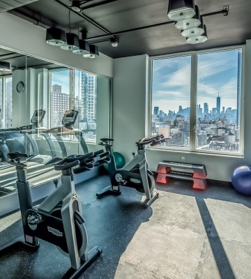 gym with equipment and window with view of the city