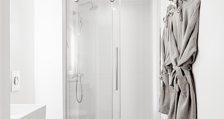 Full bathroom with glass door shower and robes hung on wall