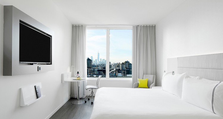 Room with double bed, tv and desk next to city view window