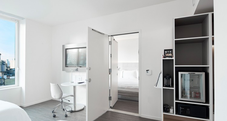 Door leading from room with two double beds to room with one king bed