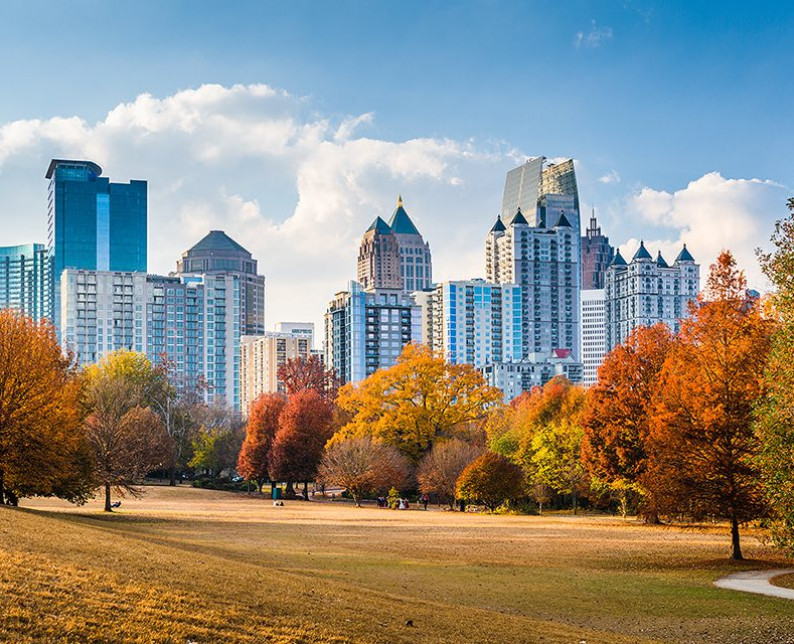 a park in fall with orange and yellow trees with Atlanta skyline in background against blue sky