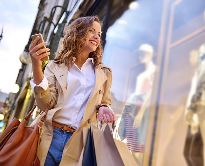 woman smiling and holding shopping bags and cell phone