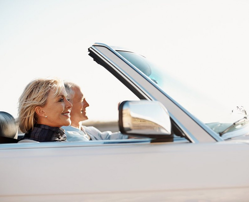 senior couple driving a white convertible car and smiling