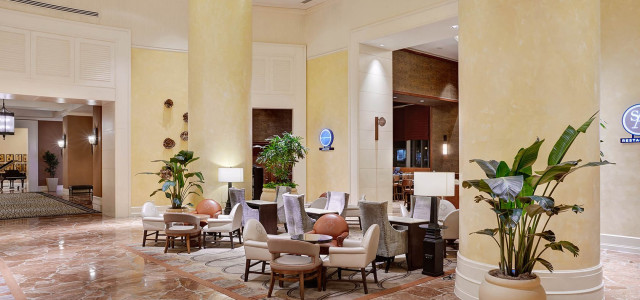 lobby seating area with high ceilings and chairs and tables on brown marble floor