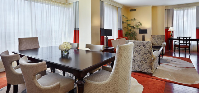 suite room with high-back white chairs at dark wooden table in front of brightly lit window