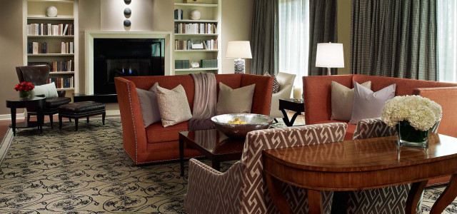 suite living area with fireplace, bookcase and red chairs on an ornate area rug