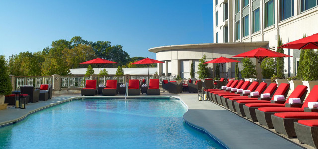 pool patio area with red chaise lounge chairs and red umbrellas by a vibrant blue pool