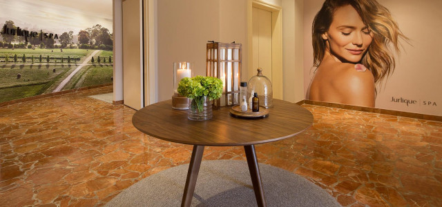 entry space for spa with round wooden table with decor on a round grey rug
