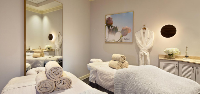 spa room with white walls and massage tables with rolled white towels