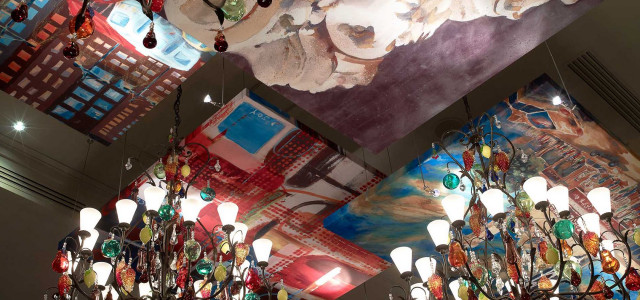 ceiling of painted canvases and multi colored glass chandelier