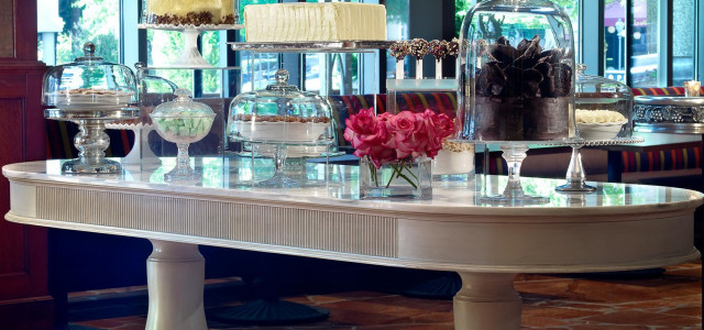 large white table with display pedestals containing cakes, pies and baked goods
