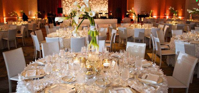 dining room setting for wedding with round tables, place settings and white lily centerpieces