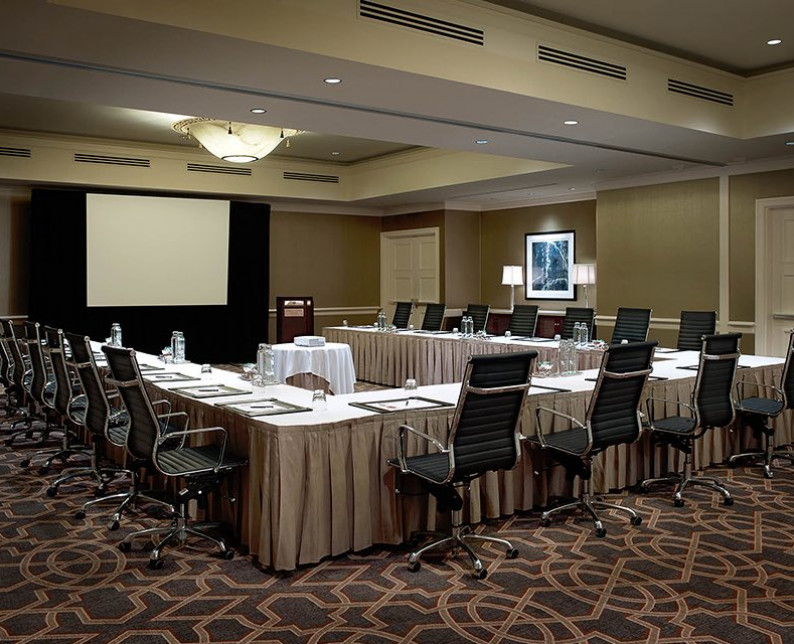 meeting space setup with long tables and executive leather chairs facing a projection screen