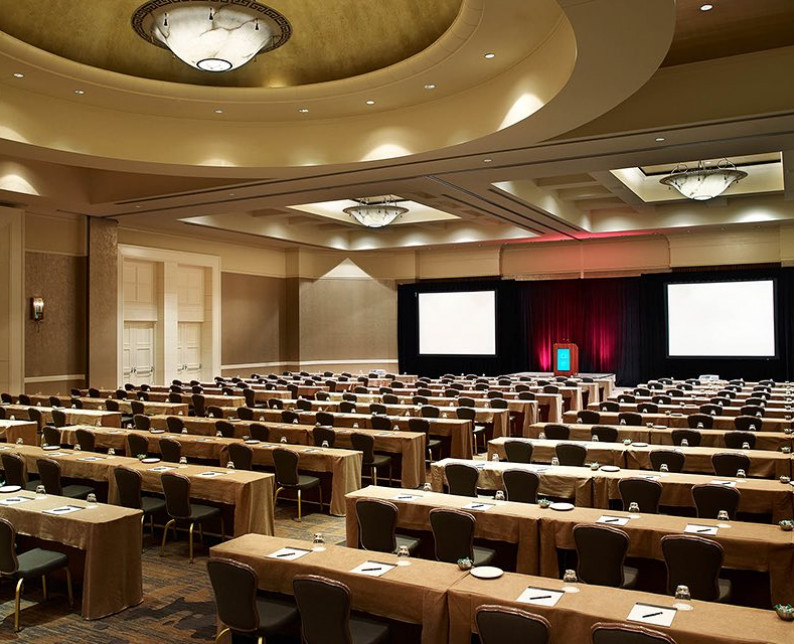 windsor ballroom setup with rows of tables and chairs facing a stage and two screens