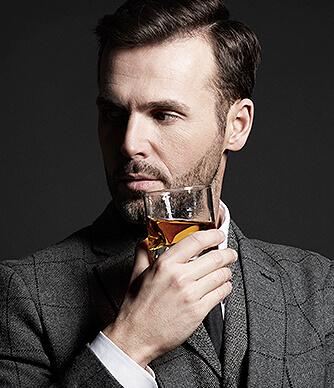 man drinking a glass of bourbon wearing a suit