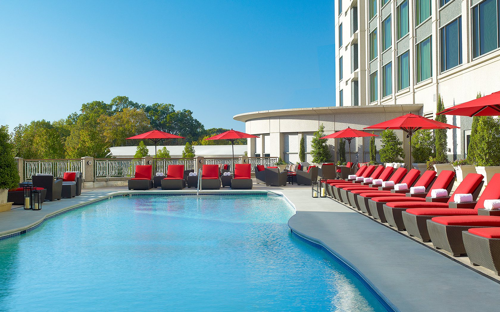 view of pool patio area with red chaise lounge chairs and crystal blue pool water