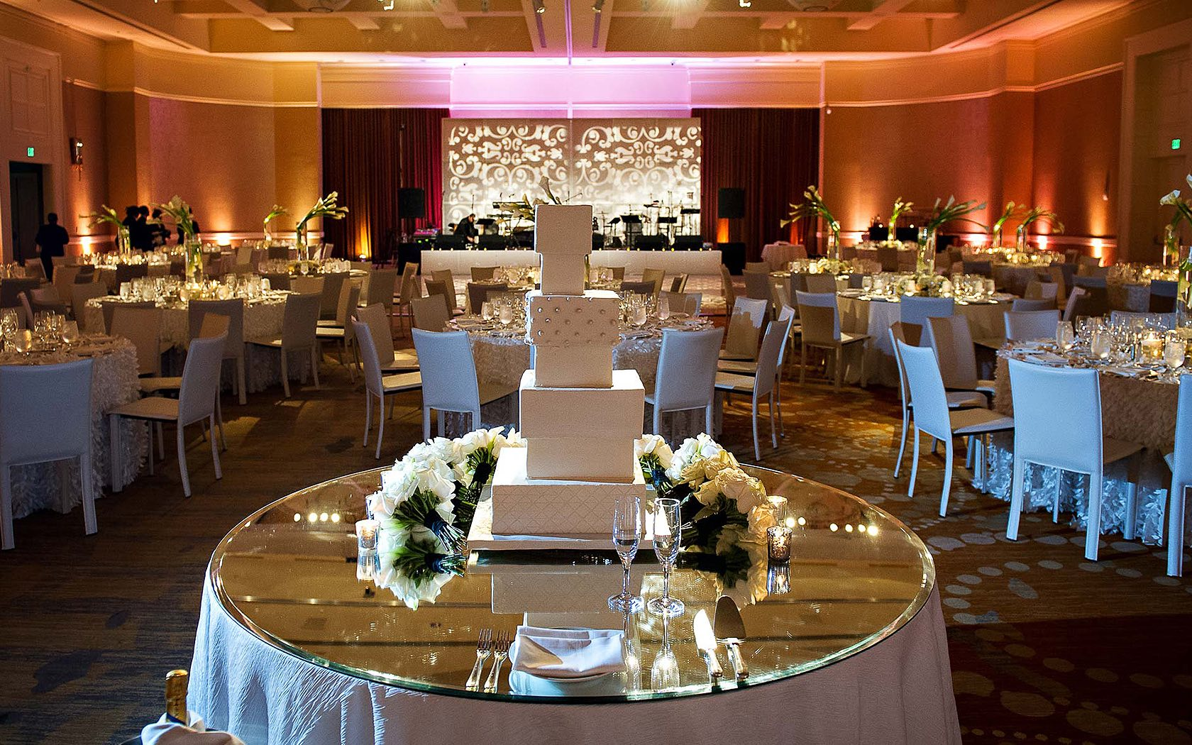 wedding event space with stage in background and round glass table with white presents in foreground