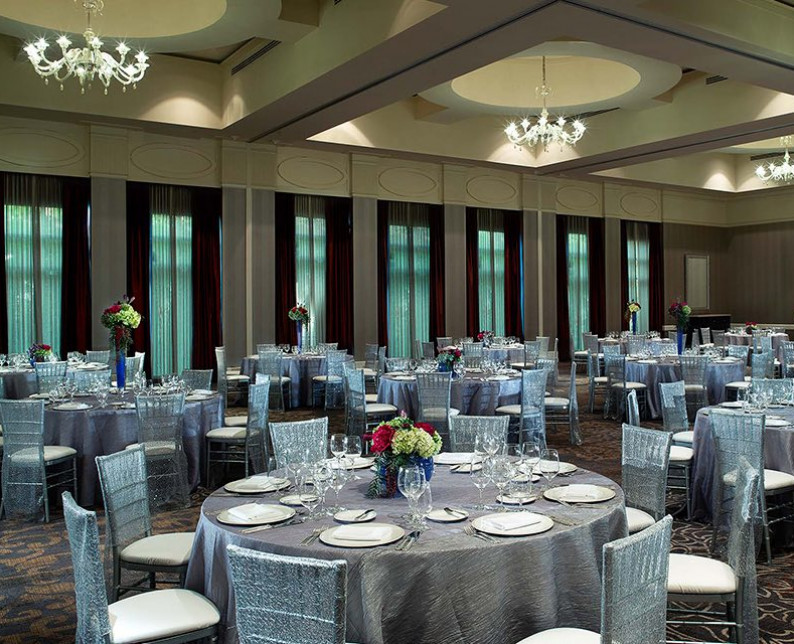 event space with round tables and place-settings on silver table cloths with silver chairs