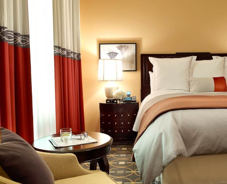 deluxe room with queen bed in beige room with red and grey curtains shining light in