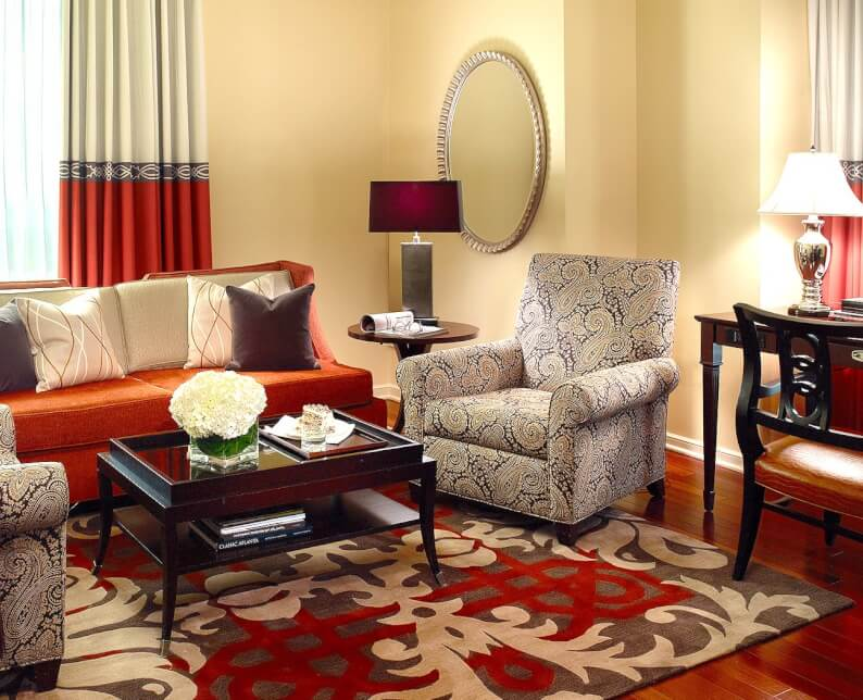 executive suite room seating area with red couch on red rug with console table and lamp