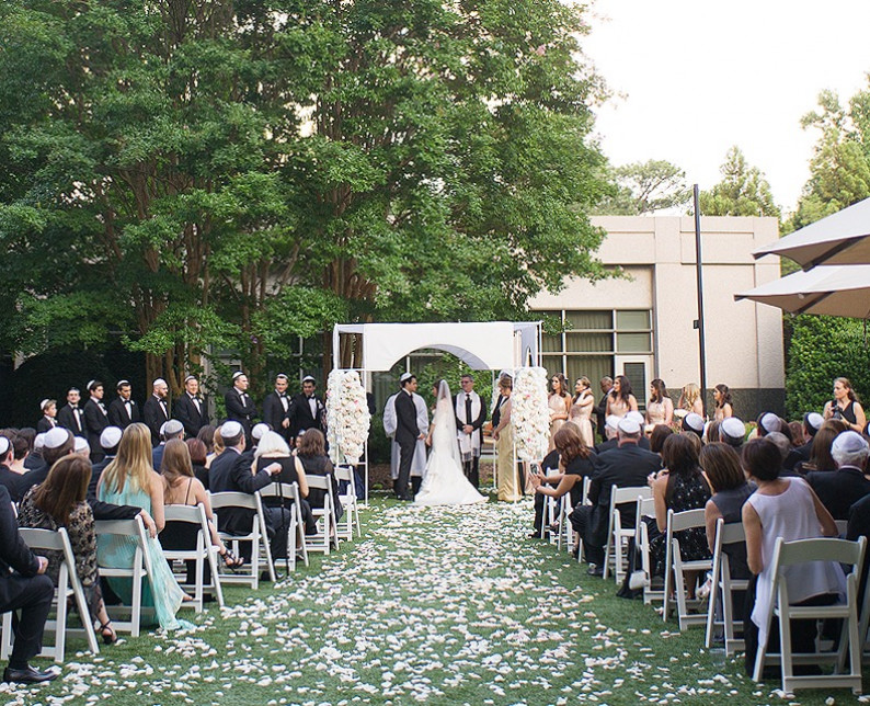 outdoor wedding ceremony with a trail of white roses