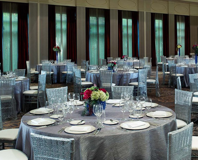 venetian ball room with large round tables and chairs with silver table cloths and white place-settings