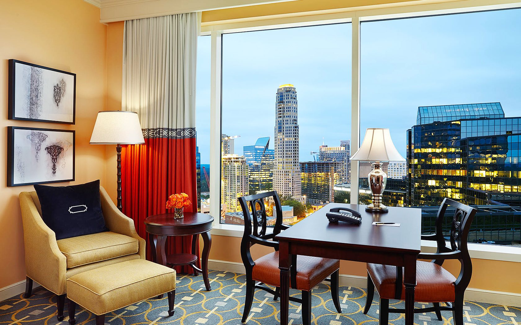 hotel room with wooden table and chairs against a view of Atlanta city skyline