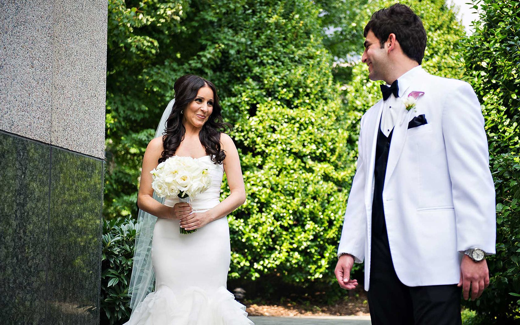 bride holding bouquet of white flowers and looking at groom lovingly