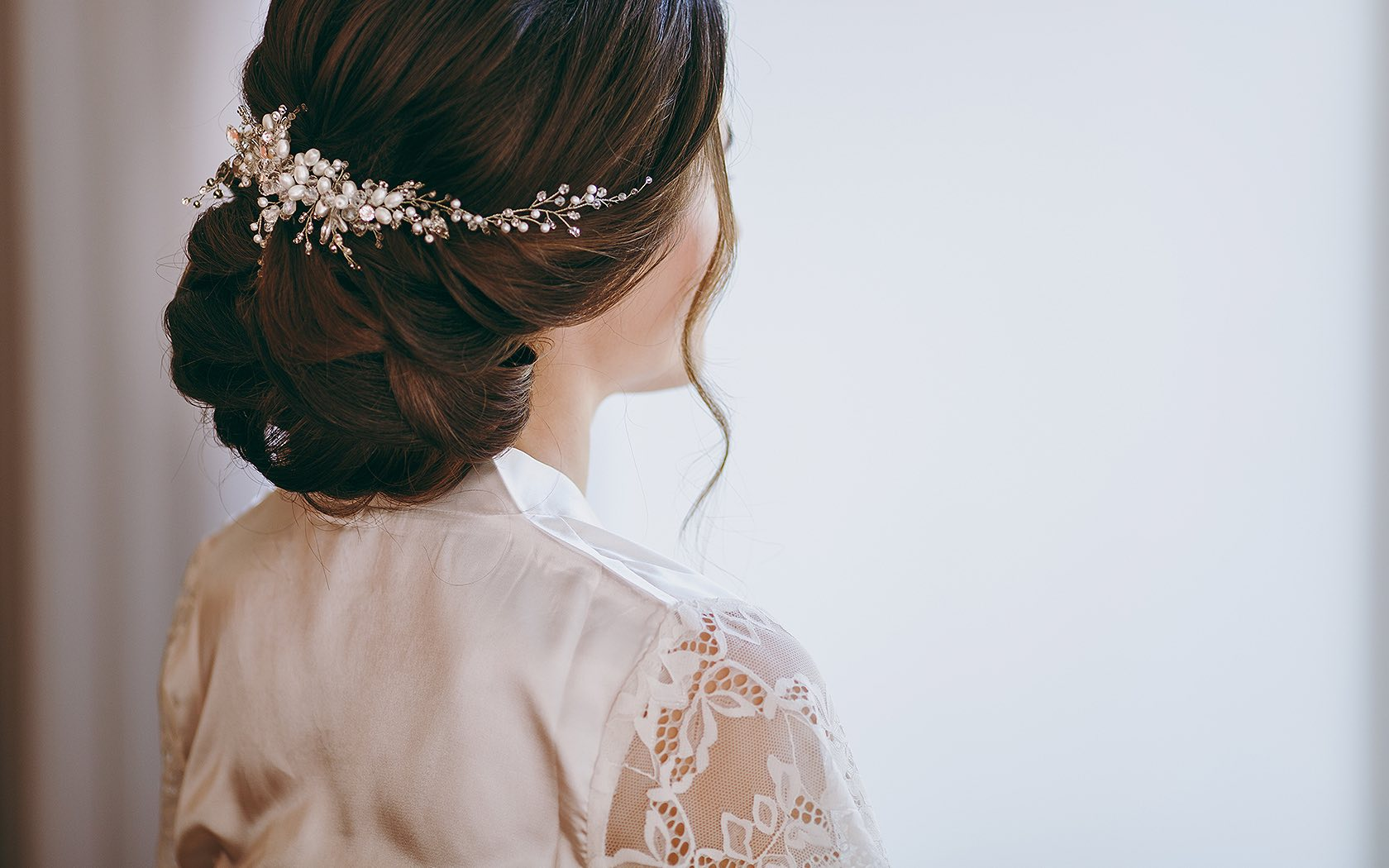 view of bride from behind the shoulder with hair in braids and curl down side of face