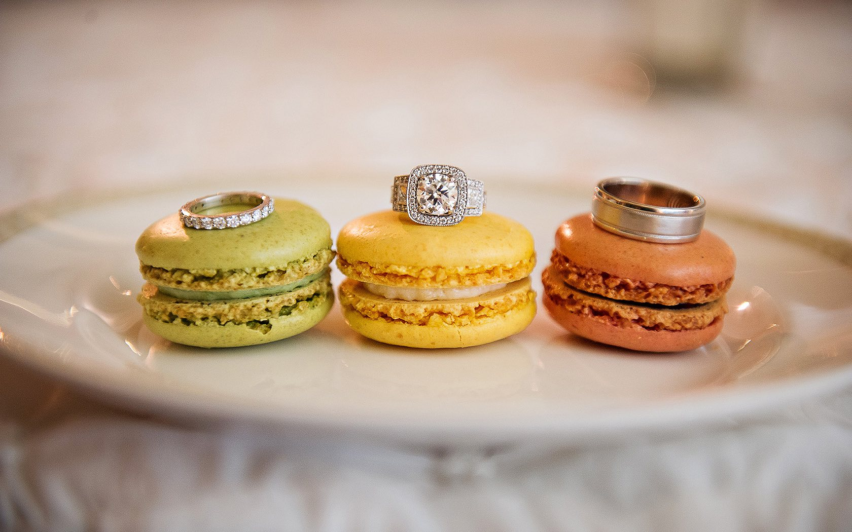 green, yellow, and brown macaron cookies with rings sitting atop them