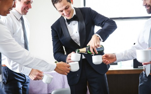 groom pouring champagne