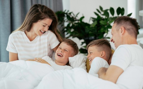 family playing on bed in hotel room