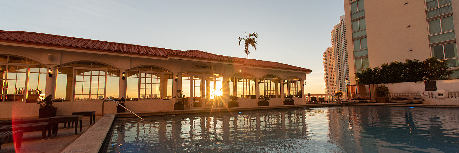 sun setting behind bluewater restaurant on the pool