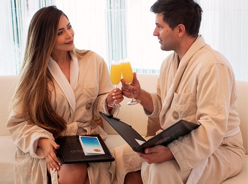 couple in spa robes drinking mimosas