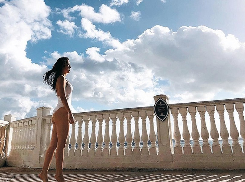 woman in a bathing suite standing on a balcony