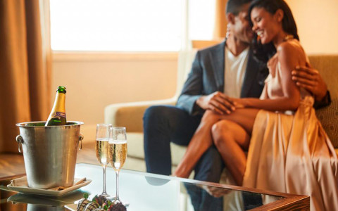 couple having champagne and sitting on a couch
