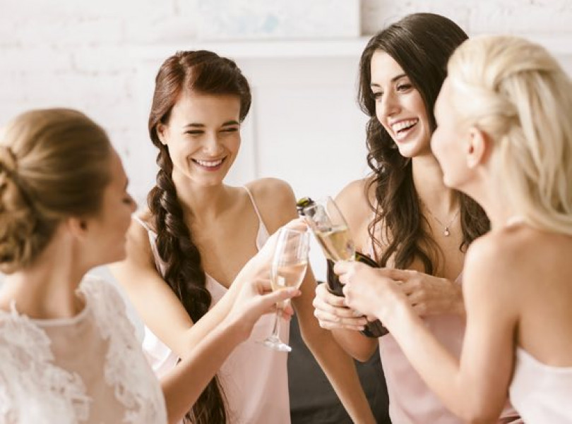 brid and bridesmaids cheering with champagne