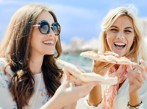 two girls enjoying pizza outdoors with miami bay in background