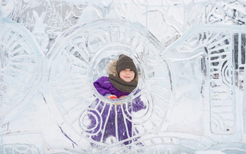 child hiding behind an ice sculpture
