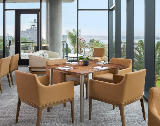 dining area with a table, chairs and large windows with views overlooking the bay