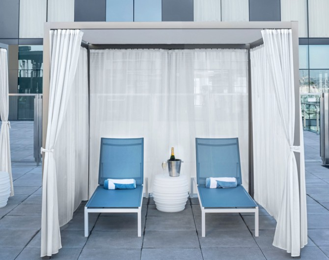 pool cabana with two blue chairs and a white curtain around it