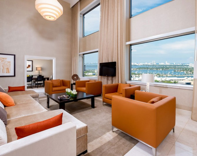 room with orange accent furniture overlooking water