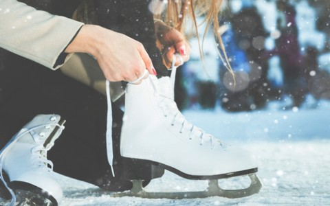 woman lacing up her ice skates